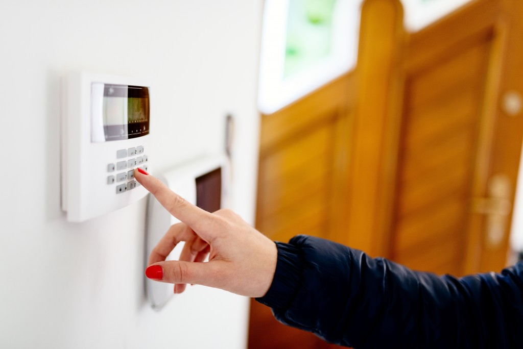 Woman entering the home alarm security code