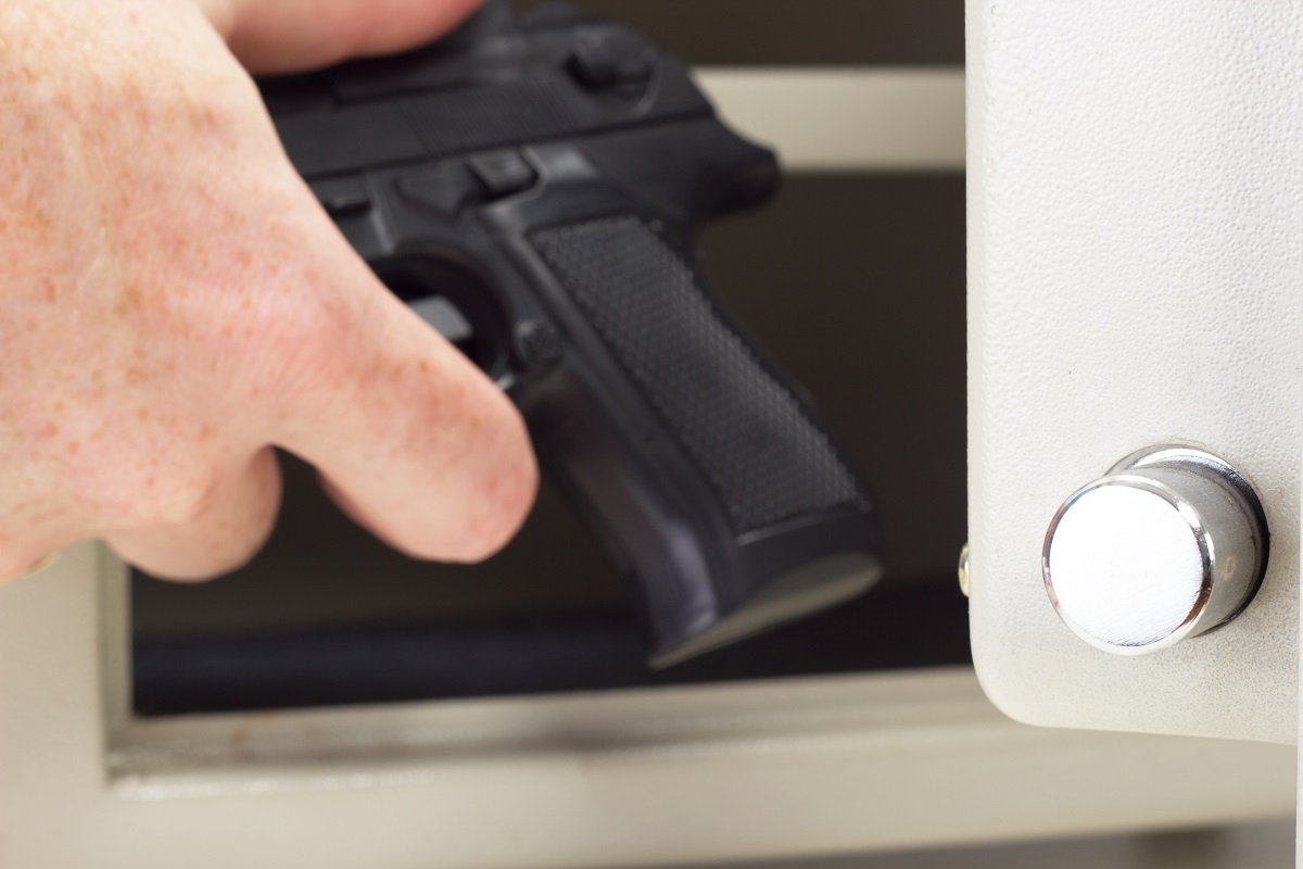 Gun owner putting the firearm in the safe