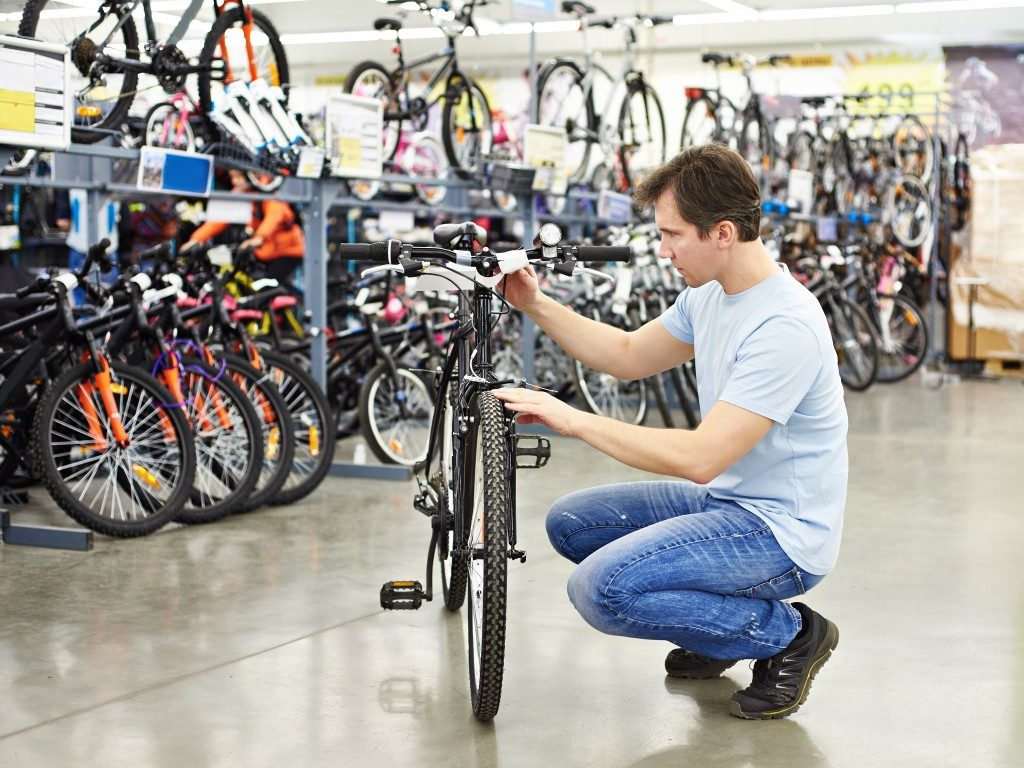 man choosing a bike to buy in a sports shop
