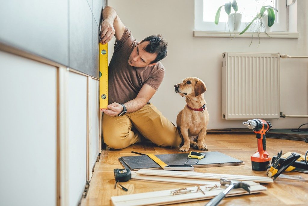 Man working on the wall of the house with a dog beside him