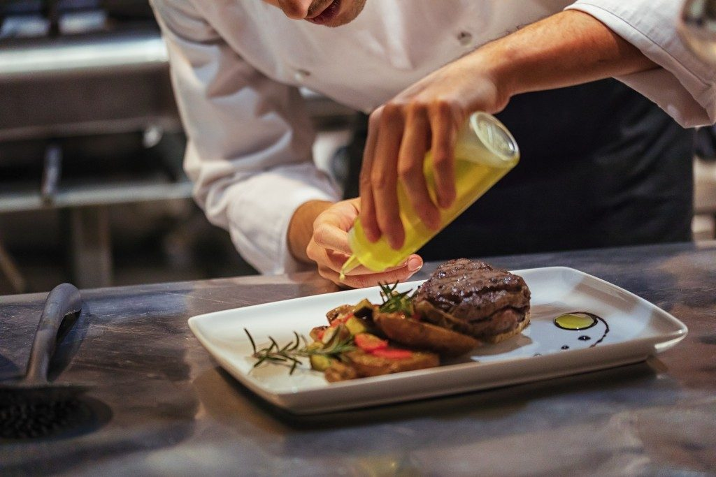chef doing a food presentation on a white plate a