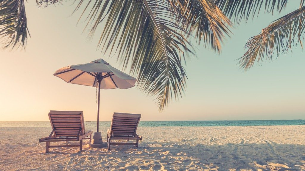 white sand with two seats and an umbrella by the beach