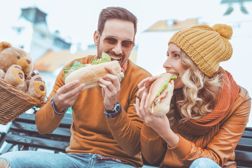 couple eating big sandwiches on a bench