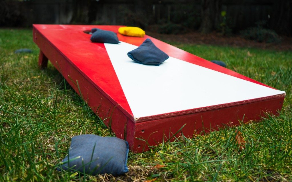 Red toss board of Cornhole game