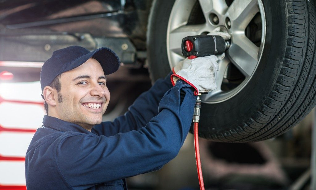 mechanic smiling while fixing tire