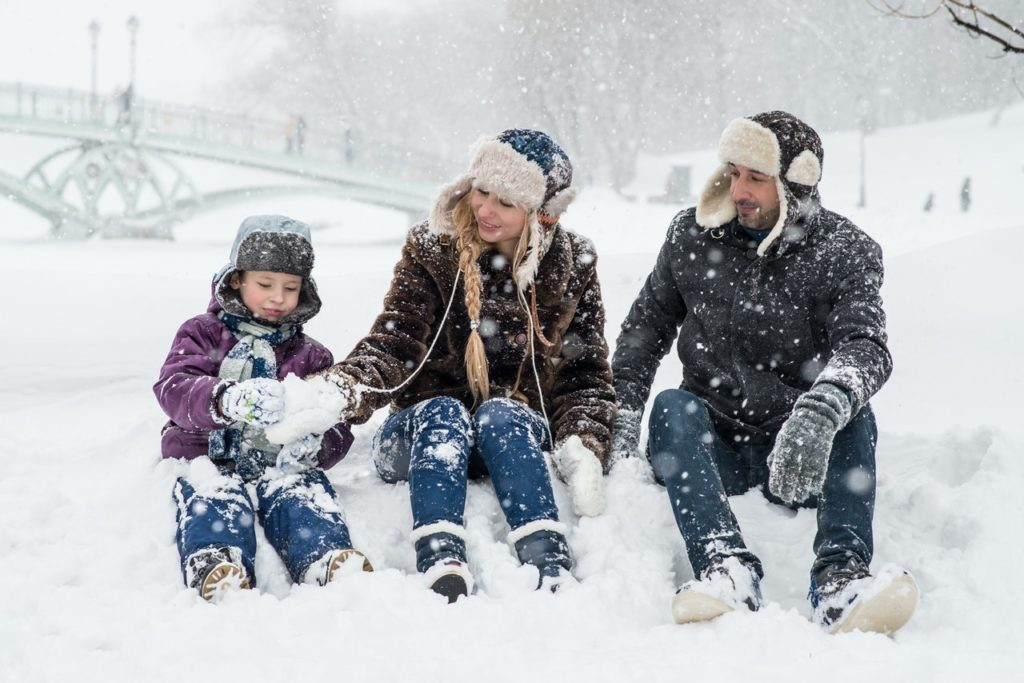 family spending time in the snow