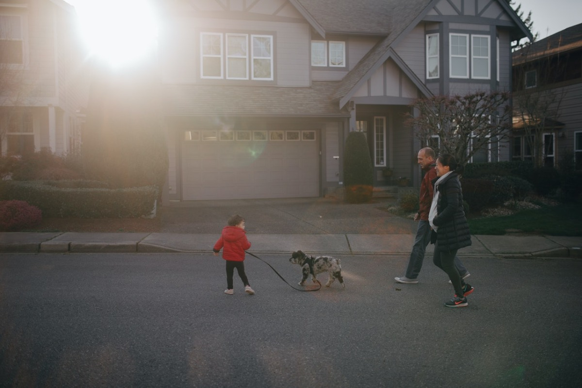 family walking with their dog