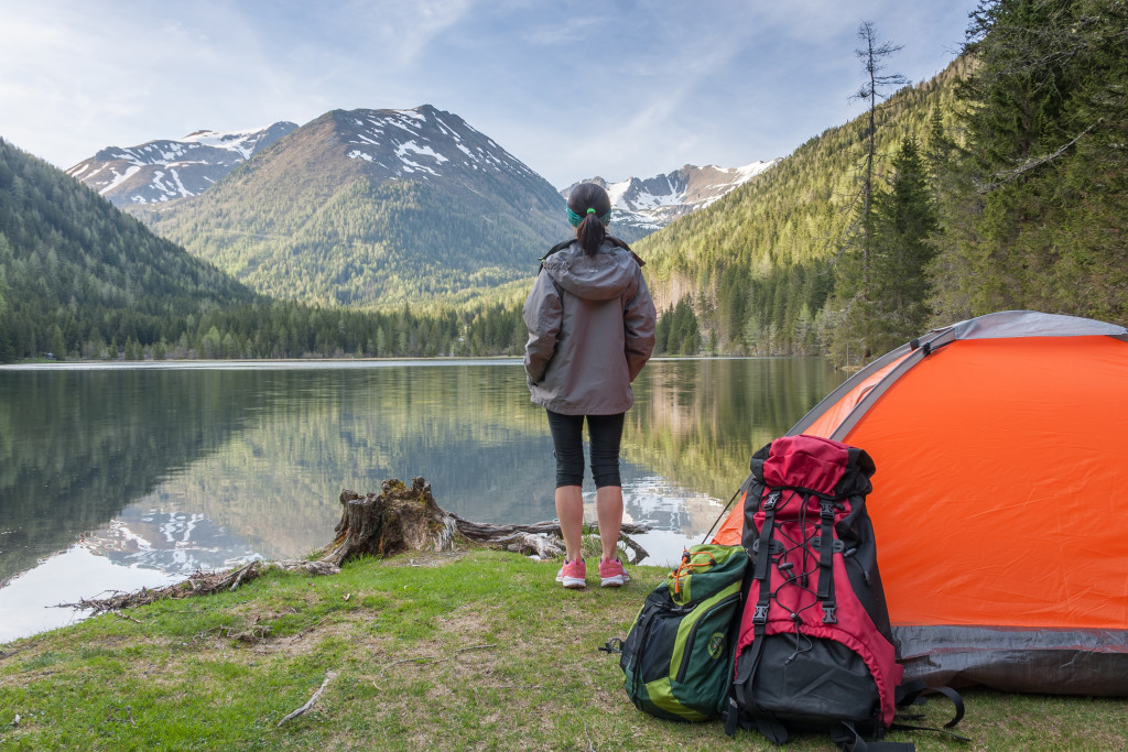 woman standing in front of a lake with a camping tent behind her