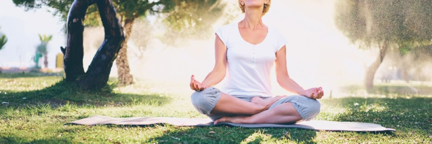 woman meditating on a sunny morning at the park